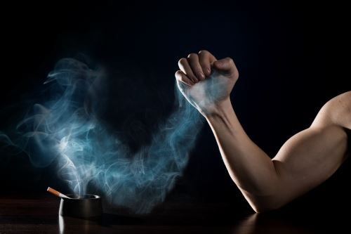 Smoke Blowing from Cigarette to Flexed Arm